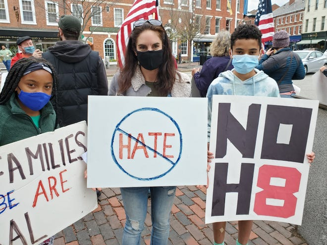 Meaghan Dunn of Kittery and her children, Jacqueline, 10, and Tyzo, 12, Diallo stand in Market Square on Sunday to take a stand against racism.