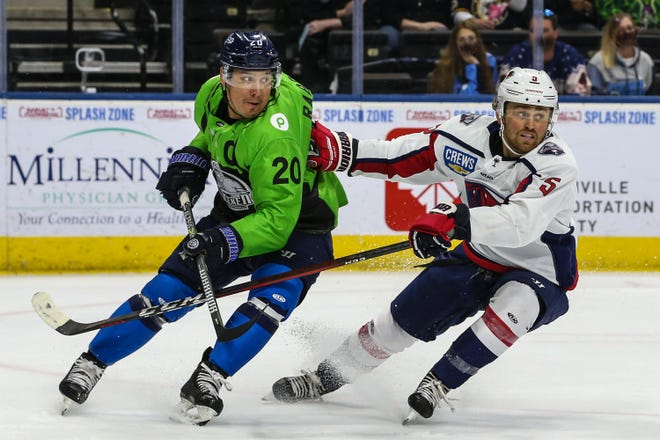 Jacksonville Icemen forward Wacey Rabbit (20) and South Carolina Stingrays defenseman Tyler Nanne (5) turn to chase the puck during the first period of an ECHL hockey game at Veterans Memorial Arena in Jacksonville, Fla., Sunday, April 18, 2021.  [Gary Lloyd McCullough/For the Jacksonville Icemen]