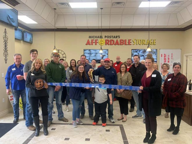 Ribbon cutting - Affordable Storage Wolfforth, 7702 FM 179, Wolfforth. Holding scissors: Isabella and Luke Diaz. Holding ribbon: Chamber Ambassadors Lisa Fraze, left, and Stacy Williams. Also pictured: Lubbock Chamber Ambassador Chairman Dalton Jantzen, owner Michael Postar and sons Dalton and Cole, and other staff, friends and Chamber Ambassadors.