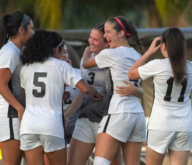 Southeastern University's Gabriela Labrador (3) is surrounded by fellow players after scoring the team's first goal against Reinhardt University during the first half of their playoff game of the NAIA Women's Soccer National Championship Tournament in Lakeland Saturday night.