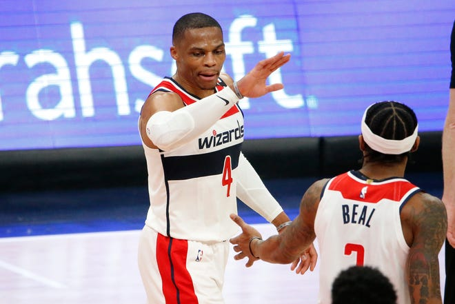 Wizards guard Russell Westbrook (4) celebrates with Bradley Beal (3) against the Pistons on Saturday.