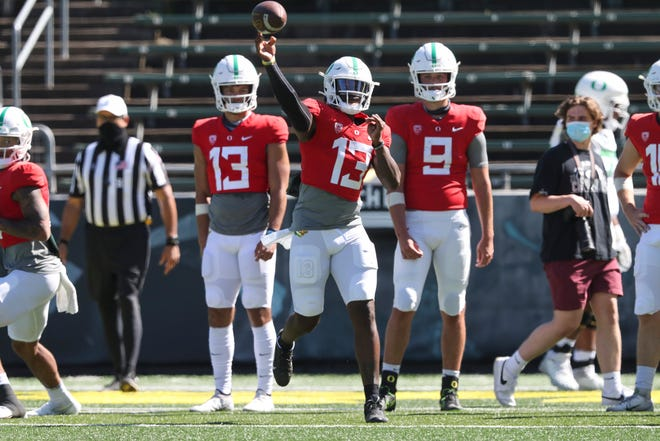 Oregon first-team quarterback Anthony Brown throws a pass while freshmen Ty Thompson (13) and Jay Butterfield look on during Saturday's scrimmage at Autzen Stadium.