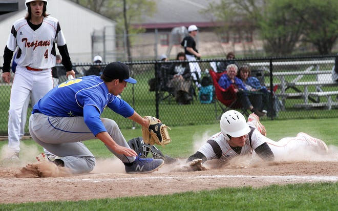 Brady Webb slides safely into home plate to beat the tag to score a run against Fort Wayne Blackhawk Christian on Saturday afternoon.