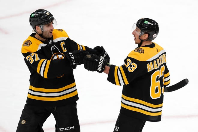 Boston Bruins' Brad Marchand (63) celebrates his open-net goal with Patrice Bergeron (37) during the third period of an NHL hockey game against the Washington Capitals, Sunday, April 18, 2021, in Boston.
