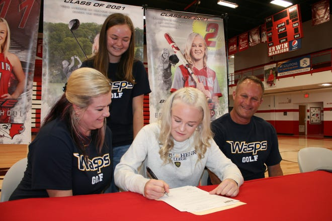 Erwin golfer Briah Frisbee (center) signs her letter of intent with Emory & Henry College on April 14, 2021, while her family looks on.