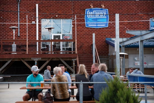 Patrons enjoy outdoor food and drinks on April 18, 2021 at Confluence Brewing in Des Moines.