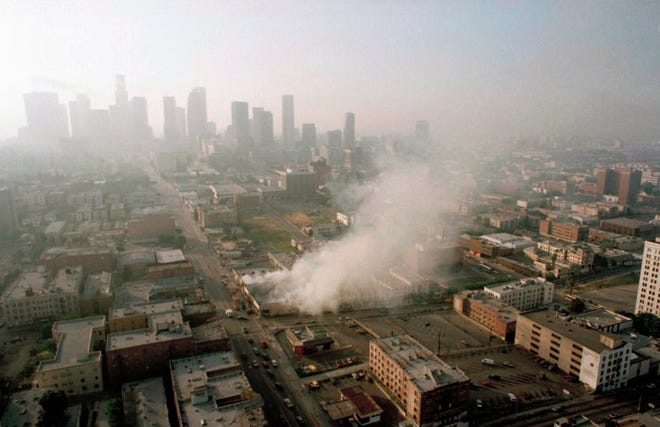 Smoke rises from a shopping center burned by rioters early on April 30, 1992, as the Los Angeles skyline is partially obscured by smoke. More than 300 fires were reportedly set after four police officers were acquitted Wednesday of the beating of motorist Rodney King.