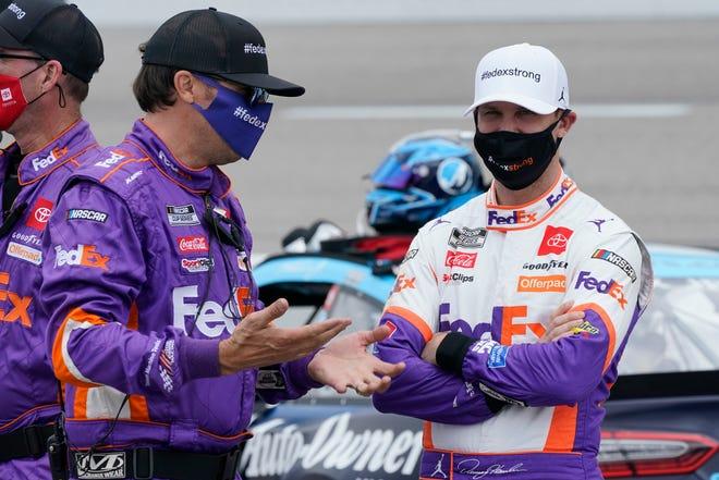 Denny Hamlin, kanan, berbicara dengan anggota kru sebelum dimulainya balapan mobil NASCAR Cup Series di Richmond International Raceway di Richmond, Va., Minggu, 18 April 2021.
