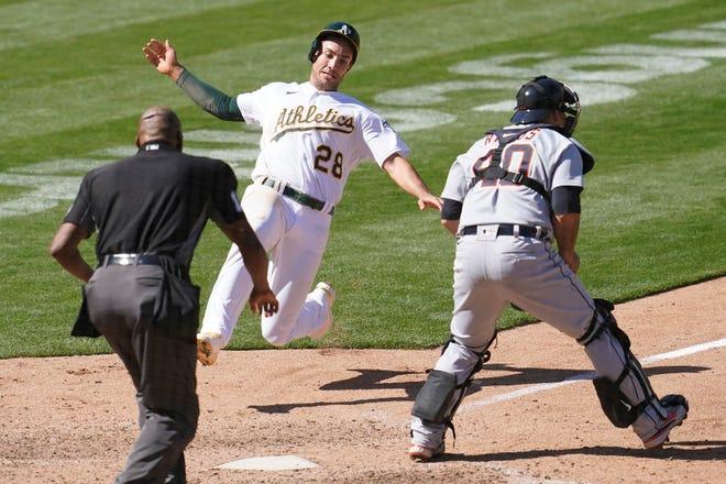 Matt Olson (28) dari Oakland Athletics meluncur ke kandang untuk mencetak gol melawan penangkap Detroit Tigers Wilson Ramos, kanan, selama inning kesembilan.