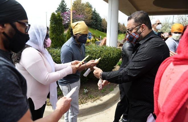 Ramandeep Sidhu, 54, dari Lyon Selatan, Amisha Datta, 22, dan saudara laki-lakinya, Aniketh Datta, 18, keduanya dari Novi menyalakan lilin mereka oleh Gurjinder Singh, 52, dari Lansing pada acara solidaritas Sikh di Plymouth Gurdwara Sahib di Plymouth, Mich. Pada tanggal 18 April 2021.