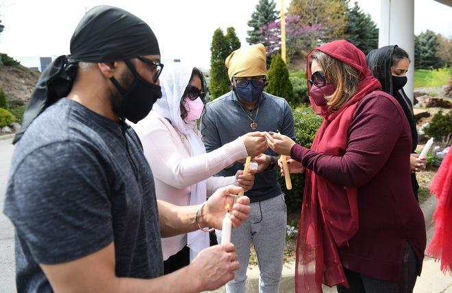 Ramandeep Sidhu, kiri, 54, dari Lyon Selatan menyaksikan Amisha Datta, 22, dan saudara laki-lakinya, Aniketh Datta, 18, menyalakan lilin mereka oleh ibu mereka, Somlika Datta, 48, dari Novi.