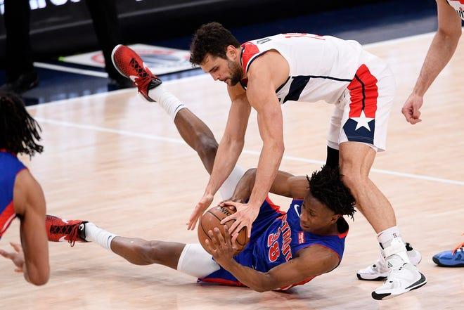Guard Washington Wizards Raul Neto, teratas, memperebutkan bola melawan guard Detroit Pistons Saben Lee (38) pada babak pertama.