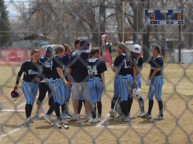 Great High High softball players surround teammate Ella Galloway (wearing helmet) following her walkoff single in the bottom of the seventh that boosted the Lady Bison past Billings West Saturday at the MultiSports Complex.