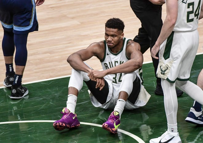 Bucks forward Giannis Antetokounmpo sits on the court after being fouled in the second quarter against the Grizzlies.