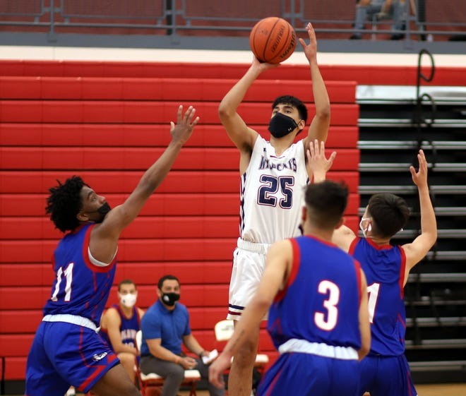 Senior Sebastian Villezcas (25) puts up a jumper surrounded by Las Cruces High defender. Villezcas scored 11 points in an 80-54 loss on Saturday.