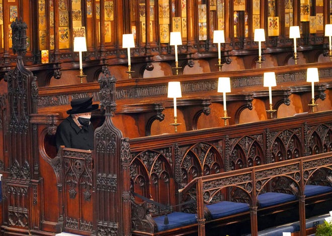 Britain's Queen Elizabeth II sits alone in St. George's Chapel during the funeral of Prince Philip, the man who had been by her side for 73 years, at Windsor Castle, Windsor, England, Saturday April 17, 2021. Prince Philip died April 9 at the age of 99 after 73 years of marriage to Britain's Queen Elizabeth II. (Jonathan Brady/Pool via AP)