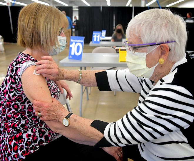 Volunteer Norma Shue, 87, prepares Barb Deller of Springettsbury Township, left, for her vaccination at the WellSpan Community COVID-19 Vaccination Site in the former A.C. Moore location on Loucks Road in York City Sunday, April 18, 2021. Norma, a volunteer at numerous organizations around York County, has volunteered at WellSpan for 17 years after retiring from the healthcare network. She was honored with a bouquet of flowers Sunday – the first day of National Volunteer Appreciation Week – from a former vaccination patient. Bill Kalina photo