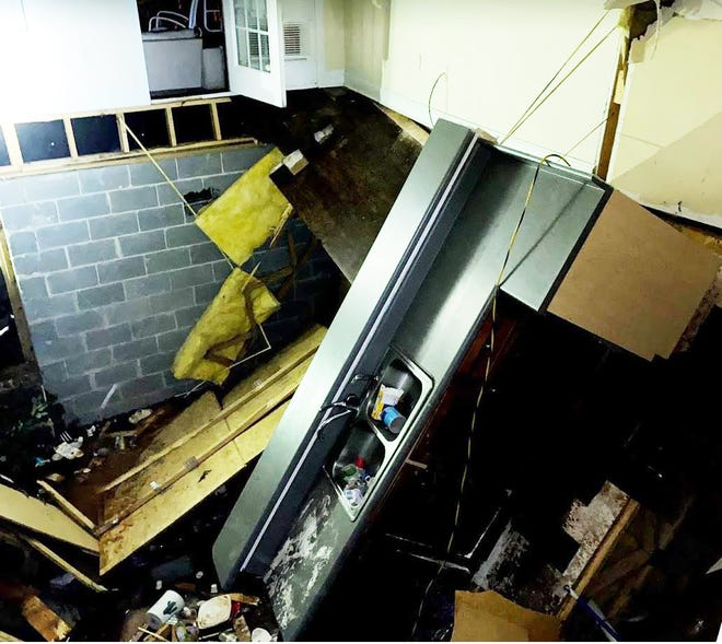 The kitchen area of the house shows one end of  the kitchen sink down in the crawlspace.