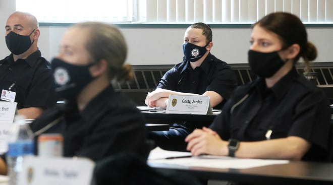 Akron Police cadet Jordan Costy, center, listens Monday during a class on crime scenes at the Akron Police training facility.