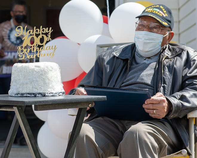 "Eddie Hill poses with his birthday cake with his nickname ""Darling"" given by his grandmother at his 100th birthday parade celebration on April 18, 2021."