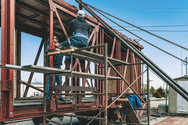 Matthew Thornton, left, Jeremy Bradford, and Darrell Bond work on the railroad freight car located outside Bartlesville's train depot. The Friends of the 940, a local volunteer group responsible for the depot display, is working to restore the car as closely as possible to its original appearance.