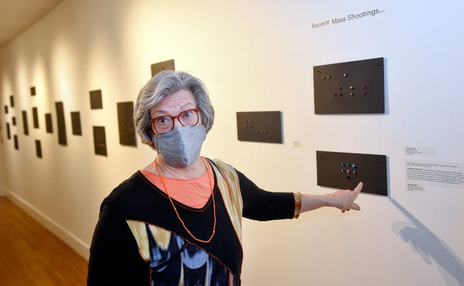 """Falmouth artist Jane Lincoln points to her graphic representations of recent mass shootings as part of her """"ENOUGH"""" exhibit at the Cape Cod Museum of Art in Dennis. After Thursday's reception, Lincoln had to create yet another piece to represent the killing of eight people at a FedEx facility in Indianapolis."""