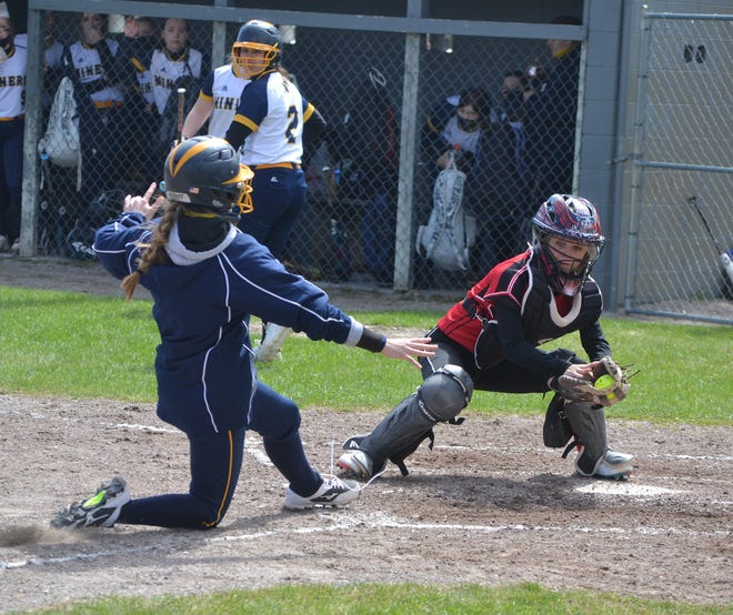 Onaway junior catcher Taylor Larson (right) prepares to tag out a Negaunee player at home plate during game one of a non-conference softball doubleheader in Tower on Saturday. The Cardinals team had an unfortunate setback later in the contest, when Larson suffered a broken tibia during a collision at home plate.