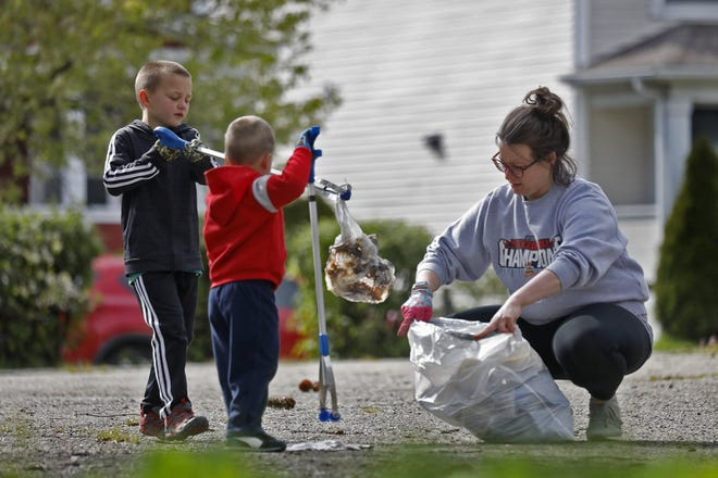 Jenny Garin picks up trash with her sons Benny and Caden on Earth Day last year.