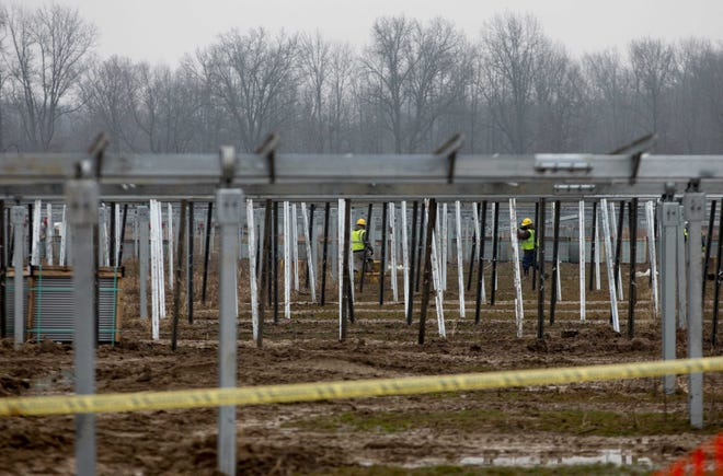 Workers build structures to hold solar panels as part of the Hillcrest Solar Project in Brown County last December. Amazon is behind the project.