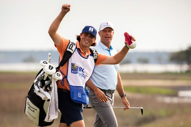 Reagan Cink raises his arms to the crowd while walking with his father, Stewart Cink, up the 18th fairway to the green during the final round of the RBC Heritage golf tournament on Sunday.