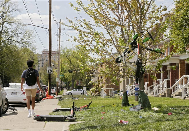 """A student walks by scattered scooters and trash on Sunday, after police estimate about 1,000 people crowded the block on Chittenden Avenue between North High and Summit streets during the annual """"ChittFest,"""" a party held the day of OSU's spring football game. Columbus police dispersed the massive block party overnight near Ohio State's campus."""