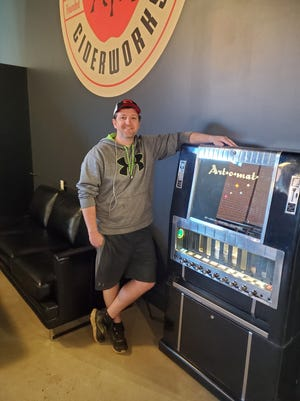 John Clowney, owner of Bull City Ciderworks, is pictured in the cidery's bar area where the first Art-o-mat vending machine in Davidson County has been placed. The machine that once dispensed packs of cigarettes now dispenses original pieces of art.