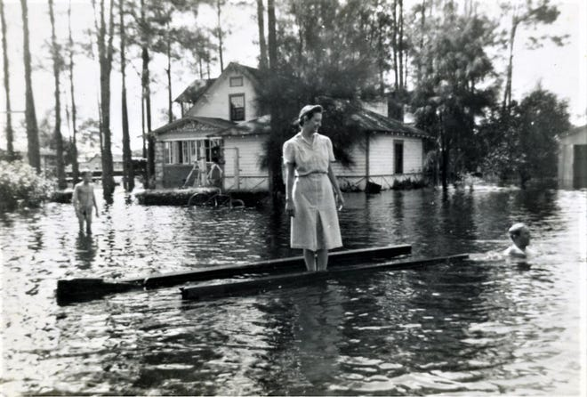 A storm caused flooding in Bunnell in 1941. Here Nevoline Cowan, a teacher, stands in front of the Holden House, which was built in 1918 by Tom Holden, the town pharmacist. Holden House is now a museum managed by the Flagler County Historical Society.