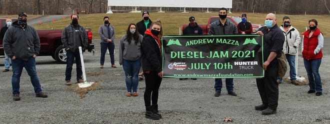 Recently, members of the Andrew Mazza Foundation and Johnson College met at the Circle Drive-in in Scranton to discuss the Andrew Mazza Diesel Jam 2021 being held on Saturday, July 10, 2021, from 9 a.m. - 2 p.m. at the Circle Drive-in.   Left to right: Front row holding banner - Penelope Ziegler, Diesel Jam Committee Member, and Nick Talarico, Heavy Equipment Program Director, Johnson College, 2nd row – Shane Pantosky, Diesel Jam Committee Member, Theresa Bandru, Golden Owl Consulting, and Diesel Jam Committee Member, Phil Mazza, Diesel Jam Committee Member, Dave Castelli, Manager, Circle Drive-in Theater, and Dawn Ziegler, Diesel Jam Committee Member, 3rd row - Chris Green, Diesel Jam Committee Member, John Wilson, Diesel Jam Committee Member, and Michael Garofalo, Diesel Jam Committee Member, 4th row -Tom Millard, Diesel Jam Committee Member, AJ Cimahosky, Continuing Education Manager, Johnson College, and Mike Novak, Chief Administrative Officer, Johnson College.