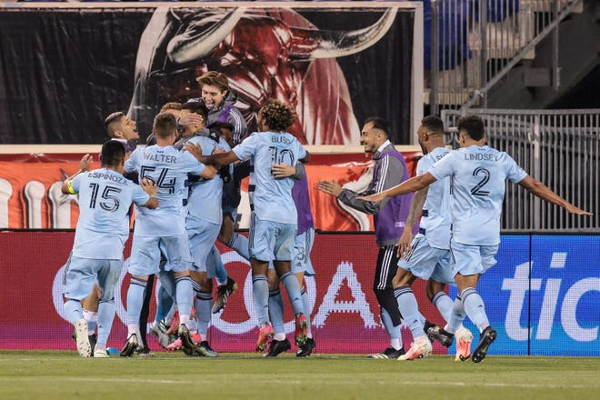 Sporting Kansas City forward Daniel Salloi (20) celebrates his goal with teammates during the second half of Saturday's season opener against the New York Red Bulls at Red Bull Arena in Harrison, N.J. Sporting KC claimed a 2-1 win.