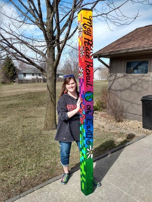 Mount Pleasant artist Annie Guldberg is shown with the finished Peace Pole she created for Mike and Abigail Heaton. The Peace Pole Project has inspired more than 200,000 Peace Poles around the world, including those at the North Pole, the Egyptian pyramids and the Hiroshima Peace Memorial.