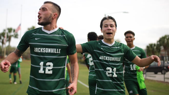 Jacksonville University soccer players Olivier Correa (21) and Joshua Moreira (12) celebrate the Dolphins' ASUN championship following their 2-0 victory on Sunday over Florida Gulf Coast.