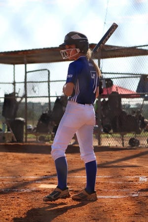 Abigale Harris looks to her third-base coach for signals during a game during her time on the travel ball circuit.