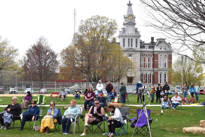 An audience takes in the first performance at the new bandshell in Cambridge on Saturday afternoon, April 17. One of the performers at School of Rock, Renee Allen, is seated in the front row, third from left. She graduated from Cambridge High School in 1999