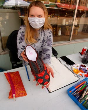 Lexi Gordon, a junior at Geneseo High School, demonstrated various forms of art, painted sneakers, wood burning and resin art work, in front of Vorac Pharmacy at Geneseo's ArtWalk.