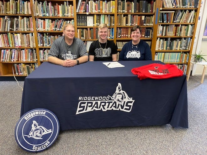 Cambridge High School senior Brendan Allen, signs a letter of intent to play baseball for Sauk Valley Community College during a ceremony on Friday, April 16, in the school library. Flanking him are his parents, Earl and Christine.