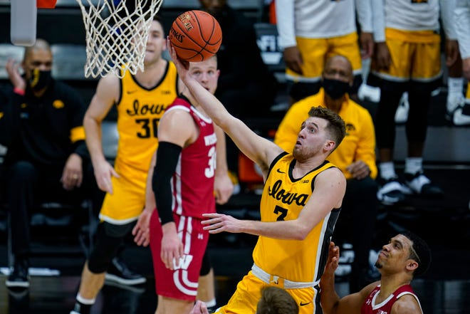 Iowa guard Jordan Bohannon (3) gets a bucket in front of Wisconsin guard D'Mitrik Trice (0) in the second half of a game at the Big Ten Conference tournament in Indianapolis, Friday, March 12, 2021.