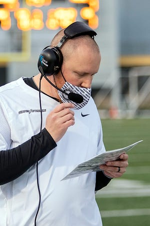 Galesburg High School football coach Michael Washabaugh talks with his staff in the booth via headset during the Silver Streaks' 27-24 loss to Moline on Friday, April 9, 2021 at Van Dyke Field.