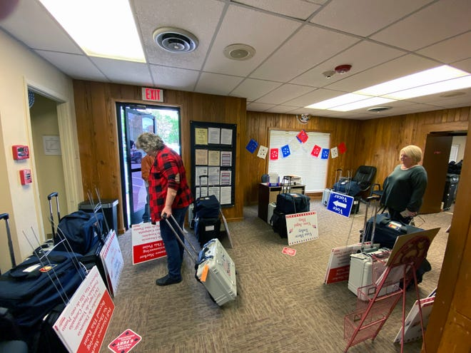 Election Judge Tammie Mitchell, at the door, prepares to leave the Grayson County Elections Administration Office on Friday with equipment for the May 1 cities and schools elections. Early voting for that began this week and continues through Tuesday of next week.