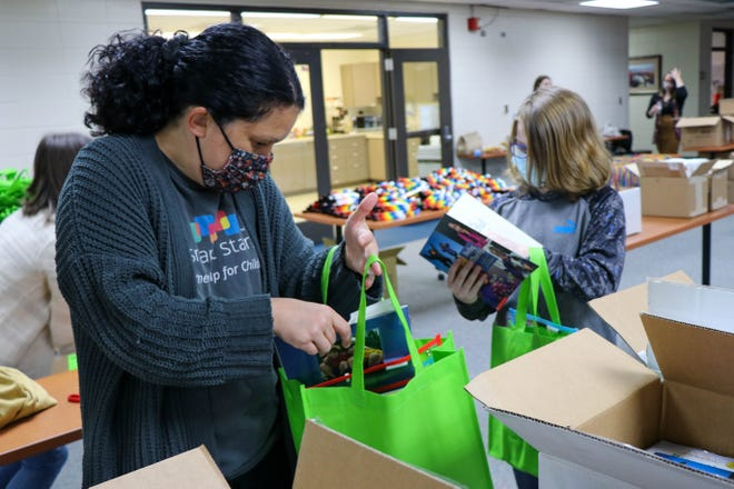 """Community volunteers put together 1,100 """"READY! kits"""" full of kindergarten readiness activities Friday. The kits includebooks, crayons, clay, safety scissors, Unifix cubes and activity sheets."""