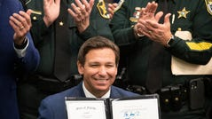 Florida Governor Ron Desantis , flanked by Polk County Sheriff Grady Judd , left and Brevard Sheriff Wayne Ivey , right holds up a bill he signed Combating Public Disorder during a signing ceremony at the Polk County Sheriff's Operation Center in Winter Haven Fl. Monday April 19 2021. ERNST PETERS/ THE LEDGER