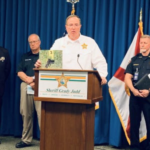 Polk County Sheriff Grady Judd holds a photo of the Taurus 9mm handgun found where officers said it was dropped by Winter Haven resident Larry Jenkins, 52, after he was shot by a Winter Haven police officer.