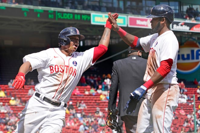 Boston Red Sox third baseman Rafael Devers (left) celebrates with teammate Franchy Cordero after scoring on a sacrifice fly during the Red Sox' win over the White Sox on Monday.