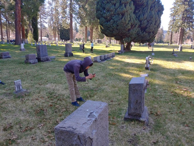 Seth Bleazard photographs a grave stone at the Mount Shasta Memorial Park Cemetery on Saturday.