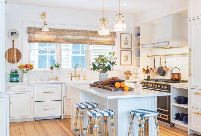 In the kitchen, marble counters from Black Diamond Stone surround a La Cornue range topped with a brass rail for easy access to cookware; pendant lights from Rejuvenation.